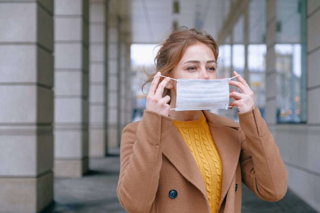 Eine junge Frau zieht sich einen Mundschutz über