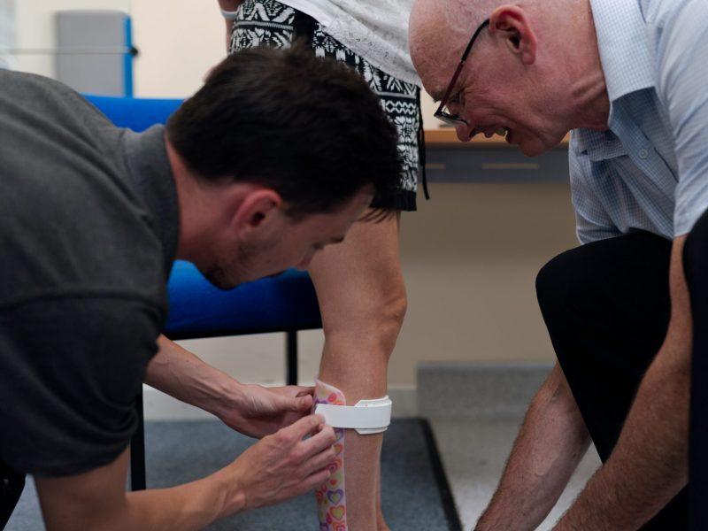 2 Menschen legen eine orthopädische Fußschiene an