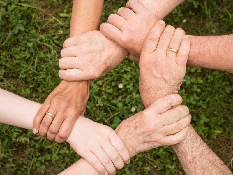 Sechs Hände greifen ineinander und symbolisieren einfach gemeinsam